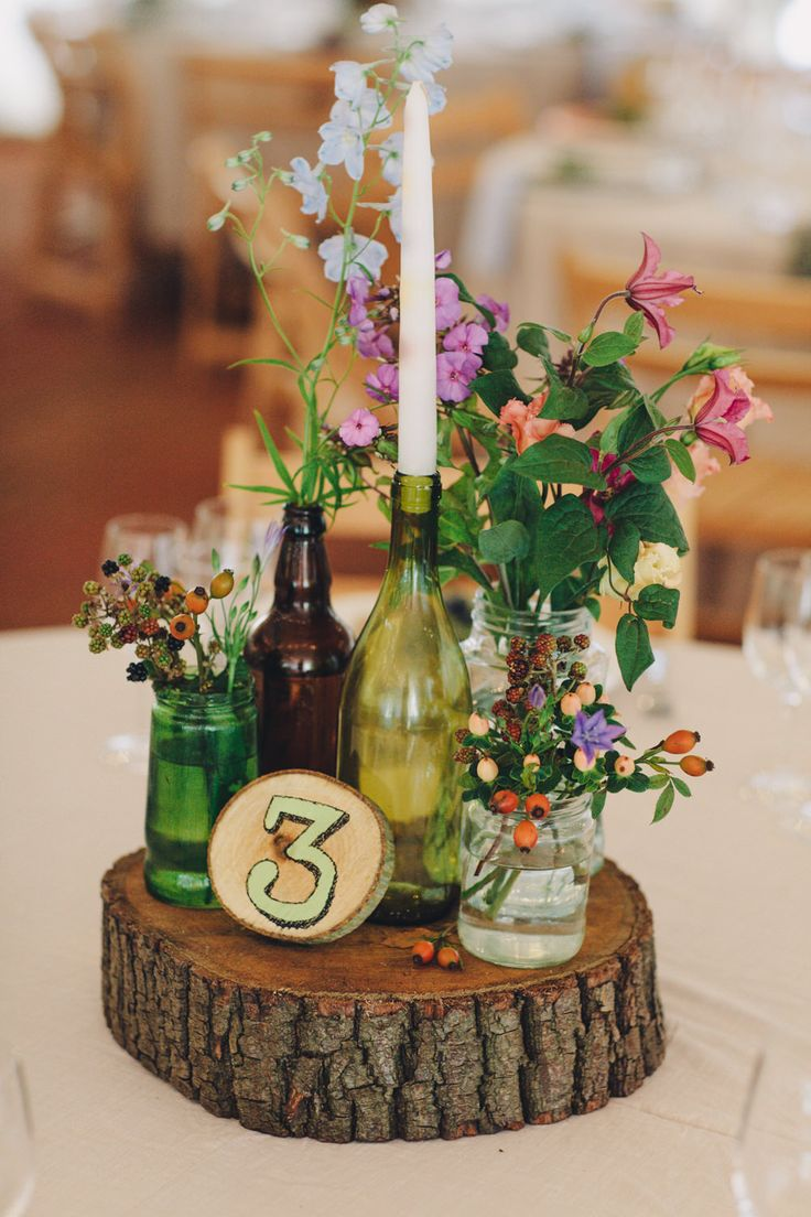 Brown and green bottles on slabs of wooden tree stumps as table centre pieces with glass jars filled with wild flowers - Image by  LM Weddings Photography - A Lusan Mandongus gown for a wedding at Wise Wedding Venue with a bright colour theme and rustic elements and photography by LM Photography.