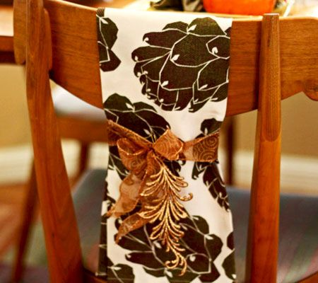 A beautiful tea towel was tied to the back of each of the chairs and embellished with a glittered orange leaf. The artichoke graphic on the towels tied in with the artichoke candle holders on the table.