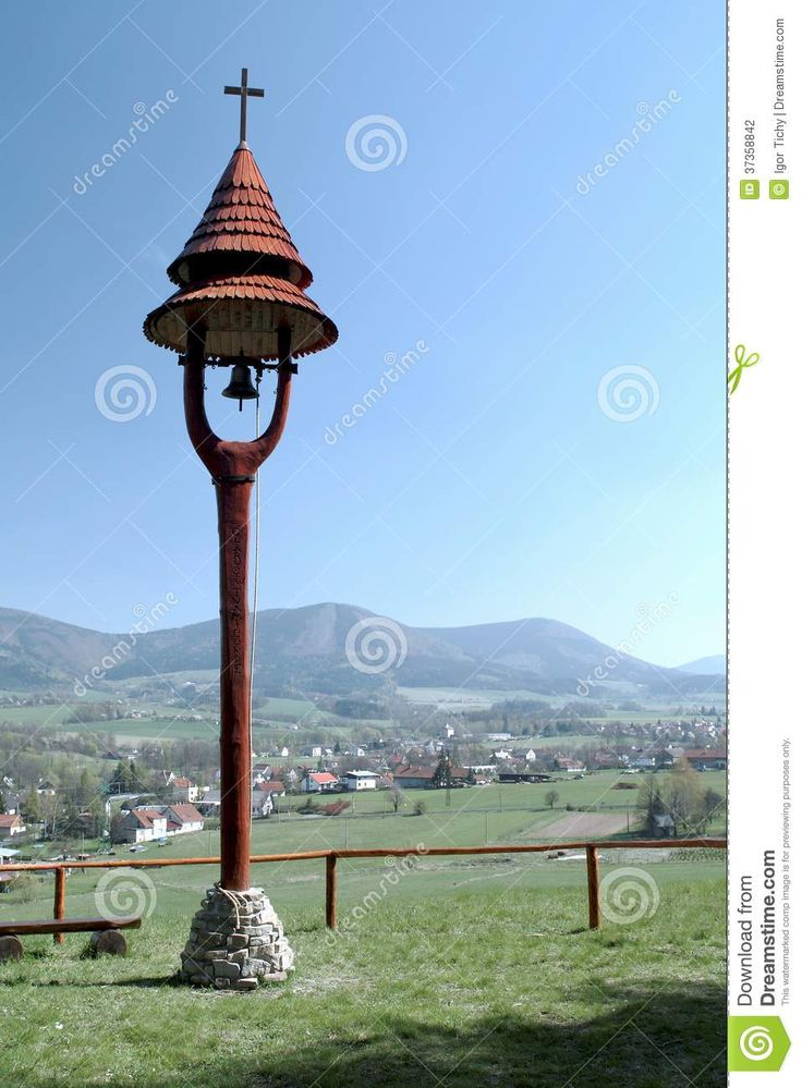 small wooden bell tower with the Beskydy mountains in the background ...