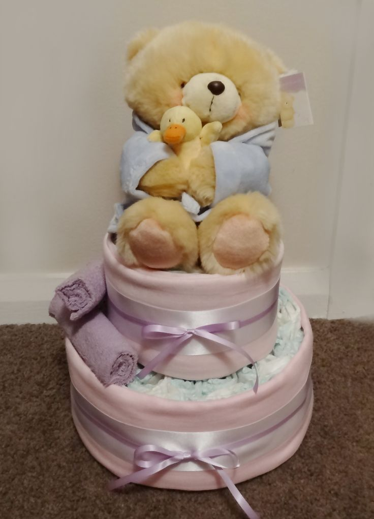 My version of a Nappy Cake. 2 purple face cloths. 2 pink muslin wraps. Newborn nappies. A teddy and thick white with thin purple ribbon. I used only two large rubber bands to hold the nappy rolls together @CaitlinJaydeC