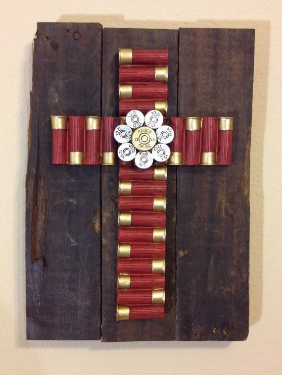 the reclaimed pallet boards are stained with a dark danish oil and then topped with a cross made from fabricated 12 gauge shotgun shells