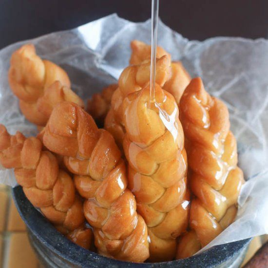 """A koeksister comes from the Dutch word koekje, which translates to """"cookie"""".2 types  version the SA syrup-coated doughnut: an Afrikaner version which is a twisted or braided shape (like a plait) and a Cape Malay version which is a spicy treat finished off with a sprinkling of coconut. It is prepared by deep-frying plaited dough rolls in oil, then dipping the fried dough into cold sugar syrup. They are very sticky and sweet and taste like honey. It serves as snack on your coffee or tea time."""