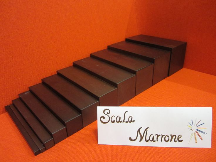 SCALA MARRONE: Si tratta di una serie di 10 prismi di legno di colore marrone, della stessa lunghezza (20 cm) ma che differiscono in altezza e larghezza andando dal più spesso al più sottile.