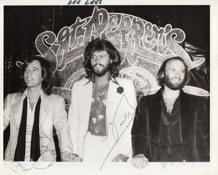 BEE GEES: Signed and inscribed 10 x 8 photograph by all three members of the pop group individually, comprising Barry, Robin and Maurice Gibb. The image depicts the three brothers standing together in half-length poses in front of a banner stating Sgt. Pepper's. Signed by Barry with his first name only and signed by Maurice Gibb and Robin Gibb with a full signature, all in blue inks to areas towards the base of the image.