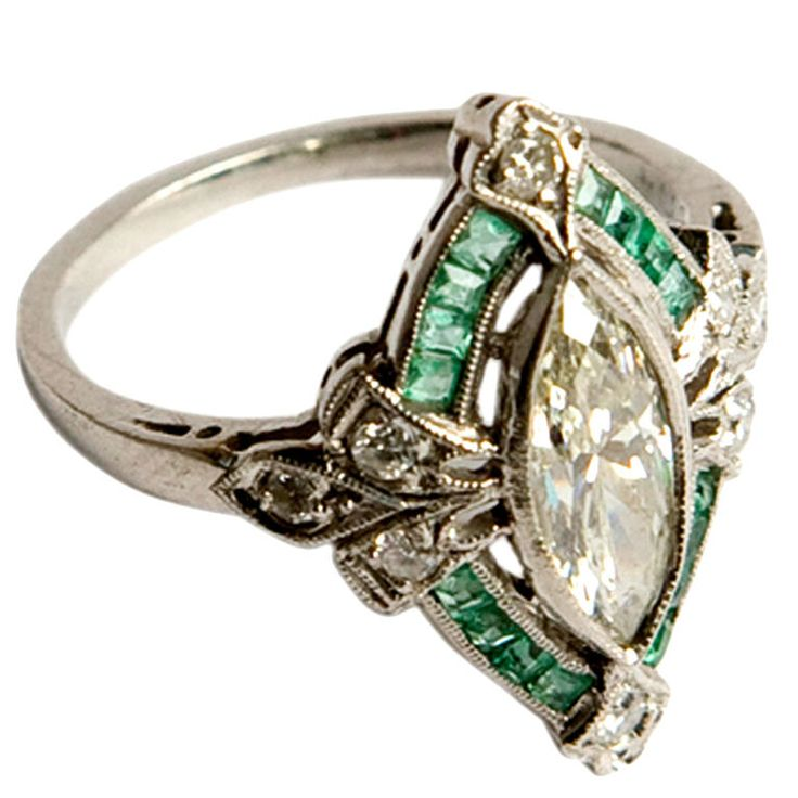 "French art deco diamond and emerald ring France 1930s The marquise-cut center diamond is surrounded by diamond ""leaves"" and channel-set emeralds. It is set in platinum."