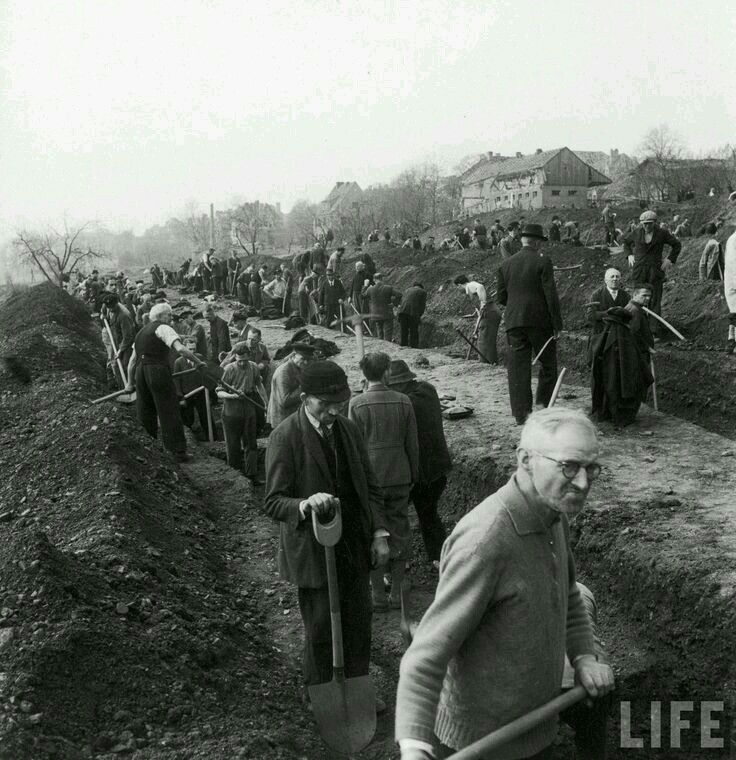 German citizens being forced by the Canadian Troops to give a proper burial to those that died in concentration camps..1945