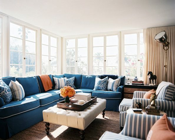 living room photo a blue sectional couch striped armchairs and a tufted ottoman
