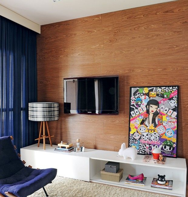 Para dar profundidade à sala, a parede da TV ganhou revestimento de nogueira-americana. O rack branco só tem uma porta, deixando a outra parte exposta.A poltrona foi garimpada em antiquário (Foto: Marcelo Magnani)