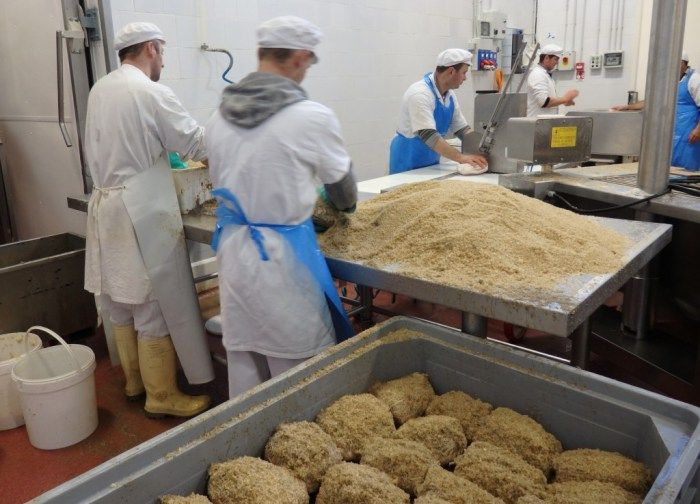 The workers in the back are putting the meat into nets. The ones in front are covering and packing them in salt. Seen on the Italian Days Food Tour.