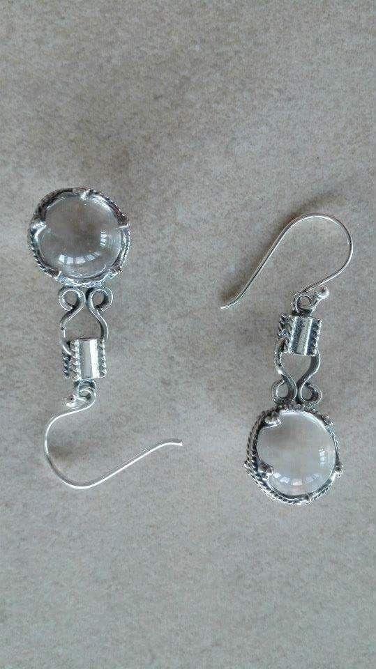 Ørehæng med krystal  Sølv: 230 kr  44 x 12 mm -  En gotlandsk sølvskat fra vikinge- tiden, ca. 800 - 1.100 e. Kr., gav inspirationen til disse ørehæng. Udover at være båret som værdi- fulde smykker, har krystallerne sandsynligvis været brugt som forstørrelsesglas. De fire ringe henviser til livets gang (f. eks. de fire årstider eller himmelsretningerne), og de 3 små kugler symboliserer treenigheden.