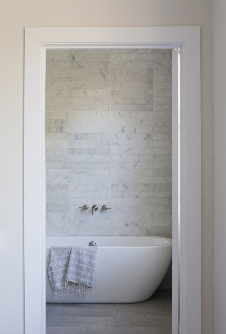Carrra marble tiles in Venice apartment by SIMO Design | Remodelista. love the idea of taking marble tiles and cutting them thinly as seen in the wall behind the bath