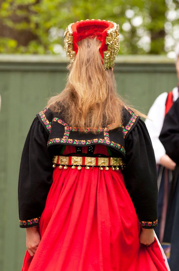 The head dress is made of layers of red wool cloth decorated with silver leaves.