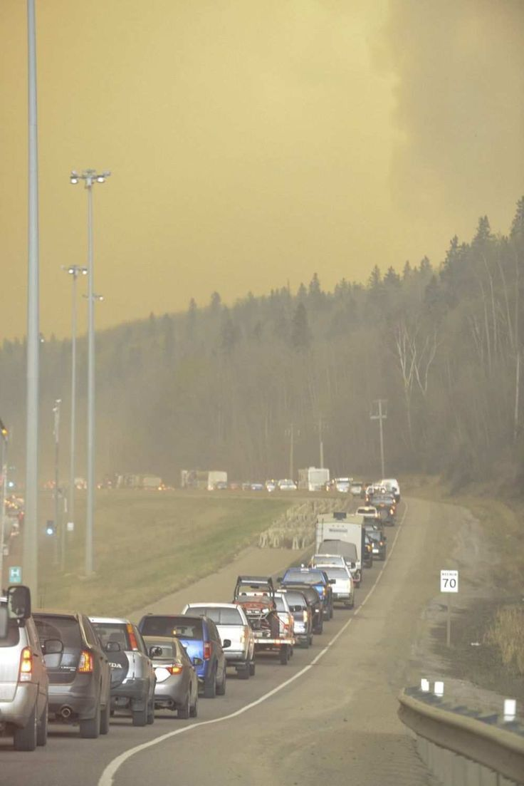 Smoke fills the air as people drive on a road in Fort McMurray, Alberta on Tuesday May 3, 2016. Raging forest fires whipped up by shifting winds sliced through the middle of the remote oilsands hub city of Fort McMurray Tuesday, sending tens of thousands fleeing in both directions and prompting the evacuation of the entire city.