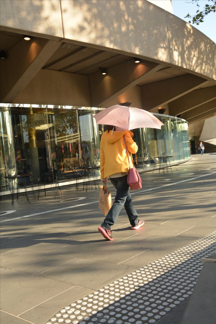 Hamer Hall  18/4/17 @ 9am  This young Asian lady was watching me with my camera as she walked by, she had her umbrella dipped to the side and i thought it would be interesting to see that as an image. The pastel tones on this woman blend with the morning sun quite delicately and she stands out with that umbrella.