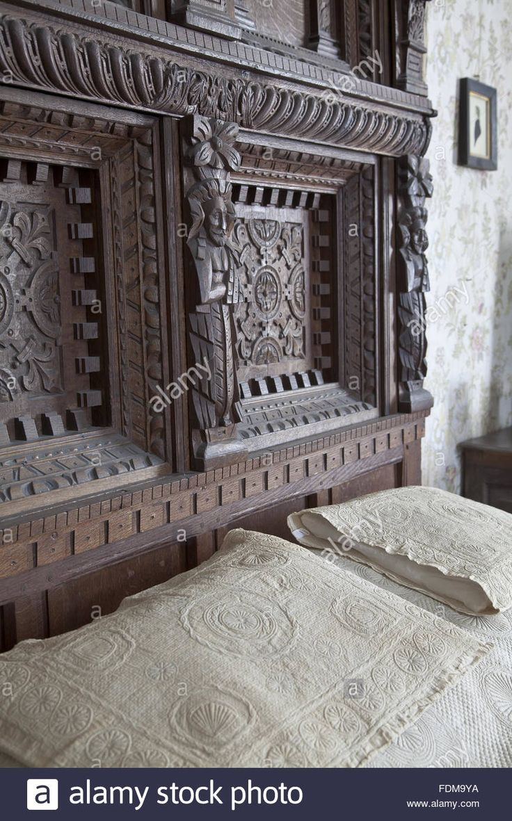 The headboard of the bed in the Cavalier Room at Chastleton House, Oxfordshire. The carved oak bed combines sixteenth and seventeenth century elements with Victorian imitations. The pillow covers are Queen Anne quilted linen. Stock Photo