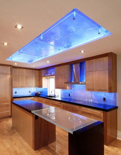 Custom glass backsplash lit by Lumilum RGB LED strip lighting that shifts  between various