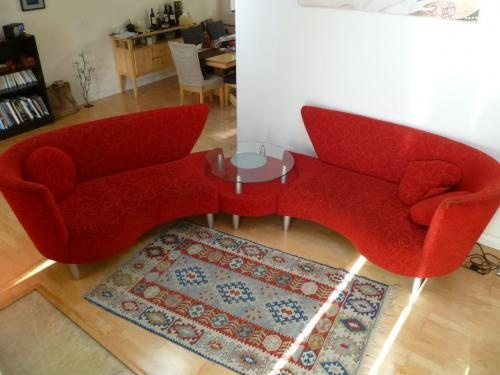 Red, sectional couch for sale. The two pieces come together at the center with a center table which has a glass top. One of a kind!! $1500.00