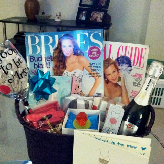 "Engagement gift basket: Bridal magazines, a ring pop, Essie bridal nail polish collection, champagne, ""mint-to-be"" mints, fun wine glass, bridal napkins and a sweet card"