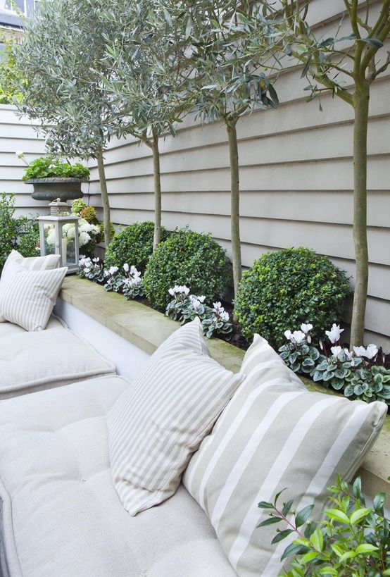 Love the idea of using a tall planter box as the back rest to outdoor seating. Looks great with all the pillows and saves space.