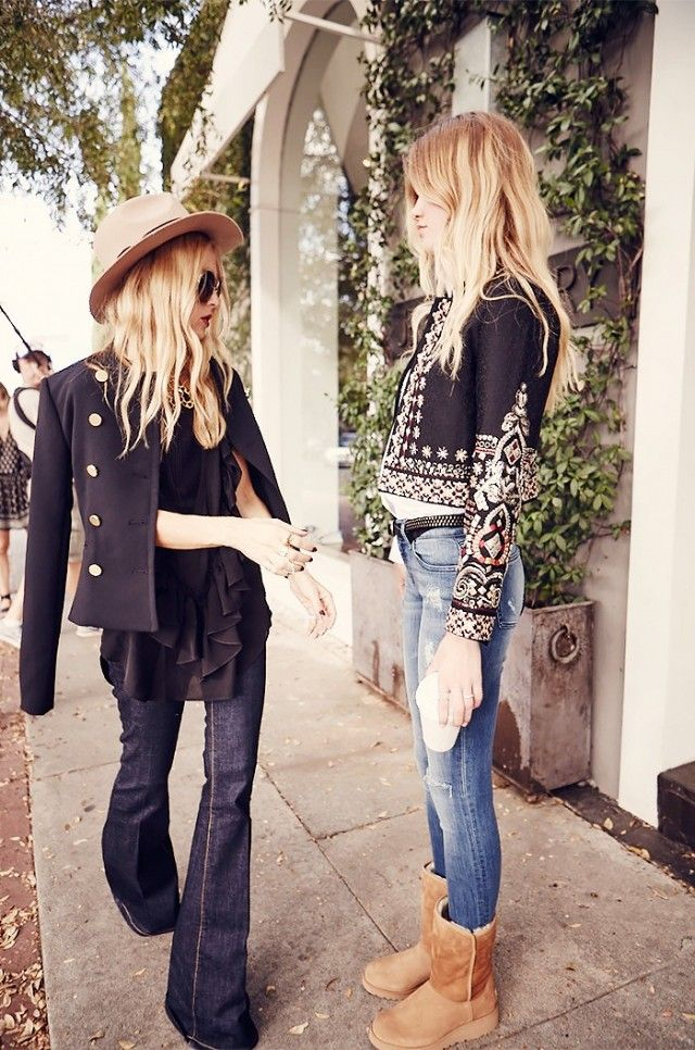 Rachel Zoe in a wide-brimmed hat, double breasted jacket, chiffon top, and flared jeans styles a model in UGG boots