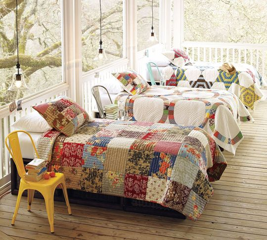 sleeping porch with eclectic quilts.  i wish i had a sleeping porch.