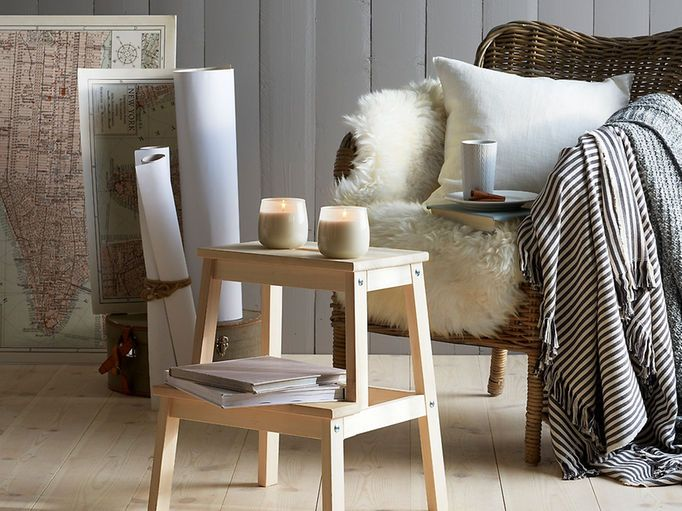 Wooden step stool with candles in front of a rattan chair draped in a sheepskin and striped throws.