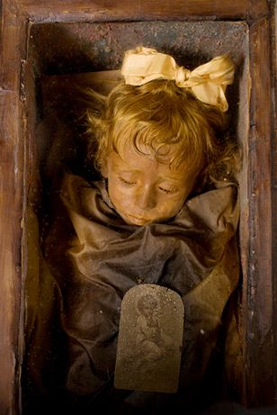 """She's one of the world's best-preserved bodies: Rosalia Lombardo, a two-year-old Sicilian girl who died of pneumonia in 1920. """"Sleeping Beauty,"""" as she's known, appears to be merely dozing beneath the glass front of her coffin in the Capuchin Catacombs of Palermo, Italy."""
