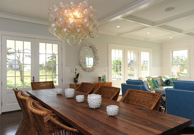 Stunning open concept dining living room with a walnut dining table lined with William Sonoma Farallon Armchairs below a glass bubble cluster chandelier.:
