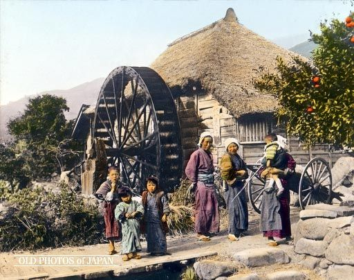 1920's, Japan. Grist Mill: Women and Children.  Three women and four children stand in front of a large water powered grist mill with a thatched roof. Water powered mills of all sizes were extremely common in Japan, a mountainous country blessed with much rainfall.