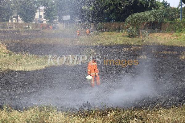 Petugas pemadam kebakaran berusaha mendinginkan api yang membakar lahan kosong di Kawasan Bisnis Mega Kuningan, Jakarta Selatan, Minggu (13/9/2015). Kemarau panjang yang melanda Jakarta, membuat sejumlah lahan kekeringan hingga menimbulkan kebakaran.
