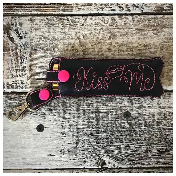 Love having lipstick on hand? Look no further than this adorable key chain holder! It holds 2 tubes of LipSense perfectly! You can reapply gloss all day without having to search for your stash! This product is made of black pleather, white thread, white snaps, and a metal lobster claw.