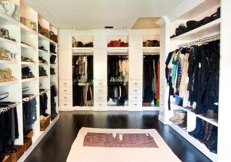 Chic walk-in closet features stacked bag and shoe shelves ...