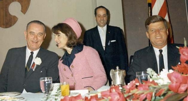 The Kennedys at breakfast in Fort Worth before leaving for Dallas. Jacqueline Kennedy shares a comment with Vice-President Lyndon Johnson.