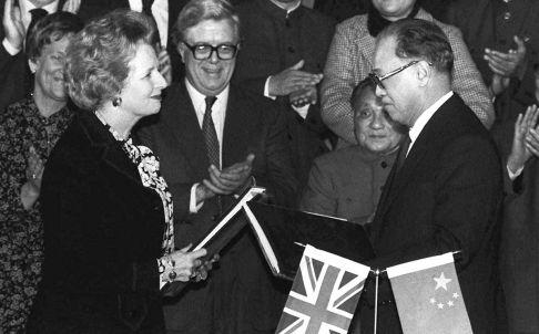 Margaret Thatcher and then premier Zhao Ziyang exchange signed copies of the Hong Kong handover agreement in Beijing in December 1984. Photo: AP