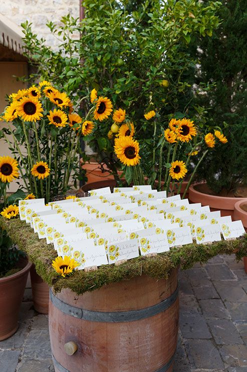 A Wine Barrel Topped With Moss Sunflowers And Recycled Corks Holds Floral Wedding Escort Cards