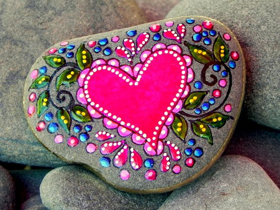~Painted Rock (sea stone) from Cape Cod.    Fairy Tale Love...tumbled on gentle ocean waves.    Raspberry red and pinks, dark and light blue, two-tone green leaves with white polka dots happily scattered...in 4 layers of water-resistant glaze inks make up this happy heart. 18K gold leafing paint edge this stone all around. This stone would be perfect placed on a desk or drawing table, a nightstand, coffee table, beside a framed photo, on a window sill, beside the tub or sink. It is lovely…