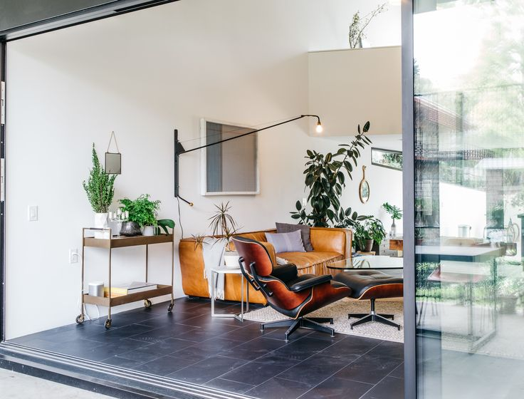 A love of midcentury design marks the couple's choice of living room furnishings, which include an Eames lounge chair and a Noguchi coffee table, paired with a sofa from HD Buttercup. The arching neck of the Prouvé Potence sconce mirrors the home's exterior form, while the large Fleetwood sliding door extends the space to the outdoors.