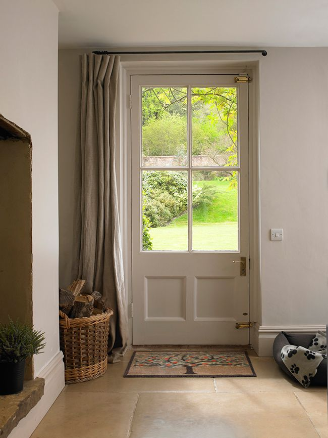Neutral countryside house interior with a lovely front door curtain to stop drafts.