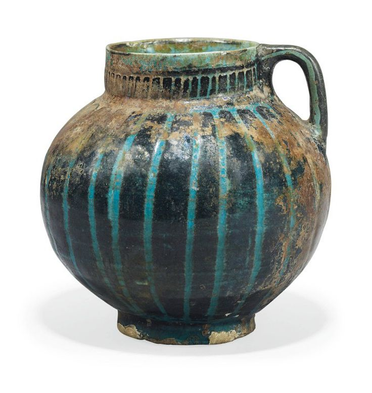 A KASHAN SILHOUETTE-WARE POTTERY JUG  CENTRAL IRAN, 12TH CENTURY  With bulbous body rising from straight foot to straight neck, with short handle, the black incised ribs under transparent turquoise-blue glaze, the handle restored, otherwise intact 5 5/8in. (14.4cm.) high
