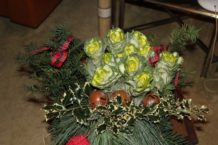 Christmas centerpiece: pine, fir, holly, cabbages, red glittering cones, bells of the gnomes and big blackberry lacquered papier-mâché and a red candle