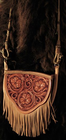 Cowgirl Cross-body Handbag by Keith Valley.  This bag is constructed with butter soft chap skin with overlaid tooling leather for the carved art.  Flowing Floral pattern on the face and a geometric stamp pattern on the back.  Handle Option either with leather strap hanger or hand braided rawhide horse bridle hanger for the shoulder strap.