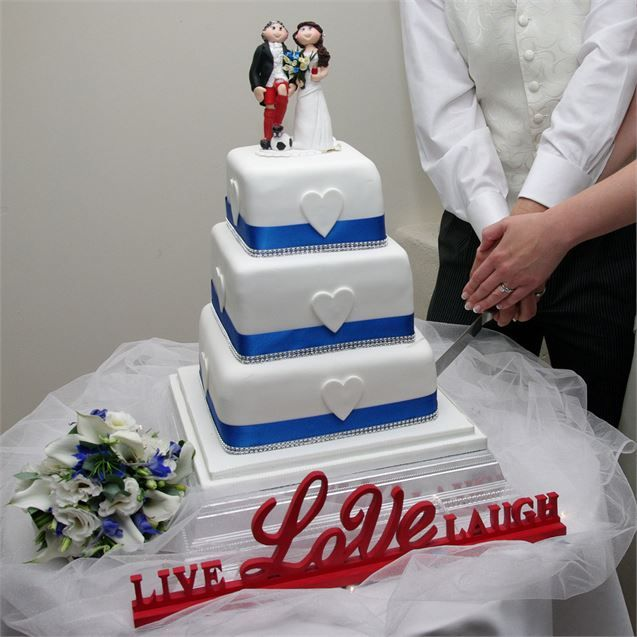 The wedding cake was three tiers of lemon and Victoria sponge, decorated with royal blue ribbon, diamantes and white hearts. The cake featured a novelty cake topper, from Toppers Delights, which was a polymer clay model of Jennifer and John. John was depicted cheekily wearing his football shorts with his wedding suit, which entertained their guests.To surprise their guests, the newlyweds hired a troupe of singing waiters, who served the guests before bursting into song and playing ...