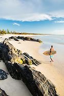 A male surfer walking between rocks and the sea on the beach at Cabarita Beach on the NSW Tweed Coast in Australia. (Copyright belongs to Fred McKie. No rights reserved. Removal of watermark or any unlicensed commercial or editorial usage will be considered a breach of copyright.)