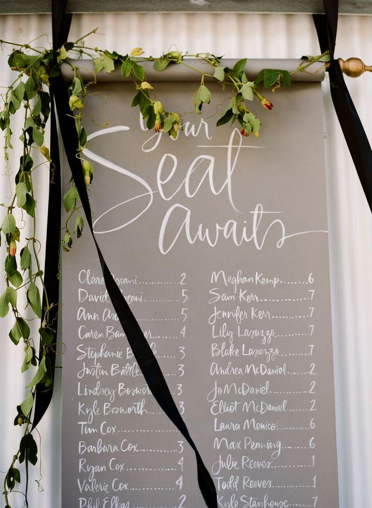 scroll table seating chart hung with flowing ribbons
