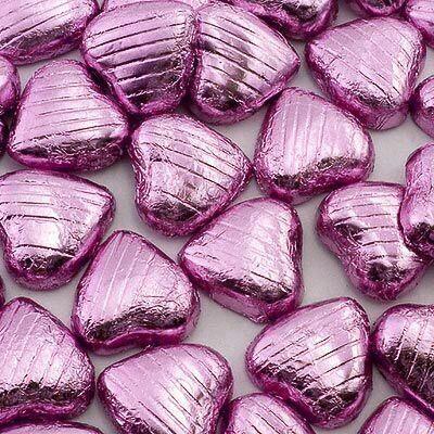 Hjerteformet lys melkesjokolade i�rosa foliepapir. Kan ogs� brukes som str�pynt p� festbordet. Best f�r mars 2014.St�rrelse:3x3cm