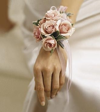 "Pink spray roses, ivy, and soft pink ribbon make up this very feminine wrist corsage. Approx. 7""h x 4""w Your purchase includes a complimentary personalized gift message."
