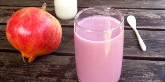 Un bicchiere di succo di melograno e latte di mandorle su un tavolo rustico di legno, insieme ad un melograno, un bicchierino di latte di mandorla e un cucchiaino