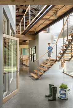 A view of the front entry's polished concrete floor and stairwell with a staircase made of reclaimed wood, new steel risers, and a cable rail system. The bridge above spans between the two volumes of the house. Caleb Johnson wanted the house to always express its own structure, so beams and posts throughout the house (whether salvaged, new hemlock, or steel) are visible. Other elements like the electric conduits going to the light fixtures are also purposely highlighted. #ModernFarmhouse
