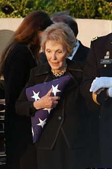 Death and state funeral of Ronald Reagan. Here his widow, Nancy, is escorted from the gravesite after receiving the flag that was on President Reagan's coffin.