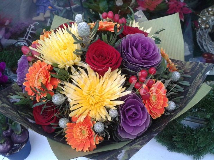 A bouquet of roses, gerberas, chrysantema, brassica and hipericum